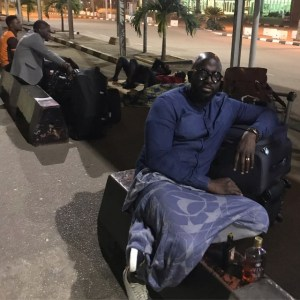 PHOTOS: Travelers sleep by roadside after staff at Abuja Airport allegedly pushed them out