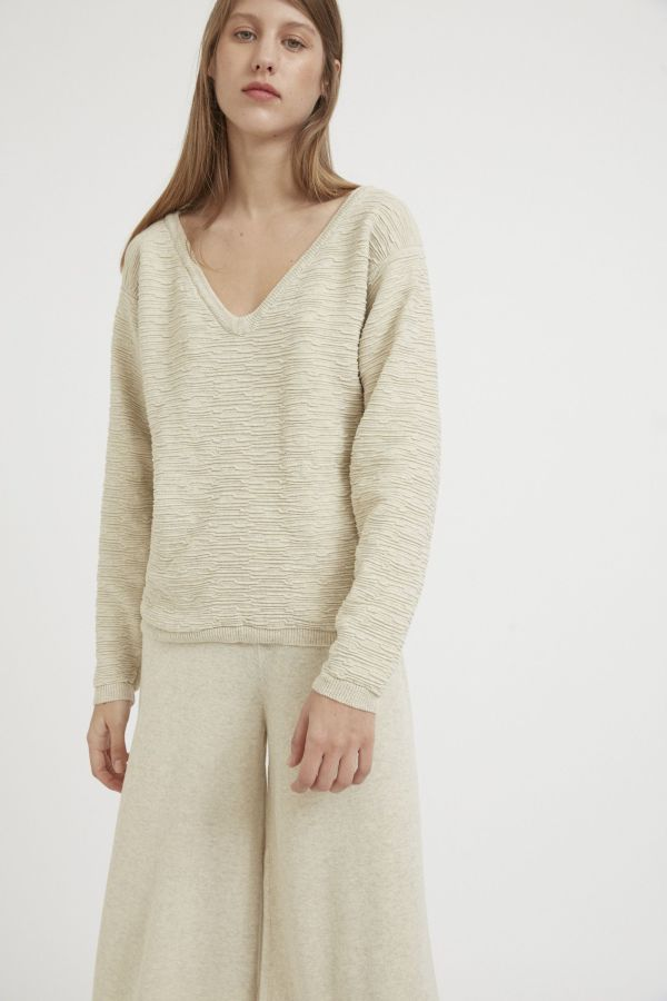 A caress from the trees Loose fitting textured sweater, with ribbed V neck, cuffs and hem. Featuring all-over embossed motifs to emulate tree bark. Made of 100% natural cotton for a cosy and unique style.