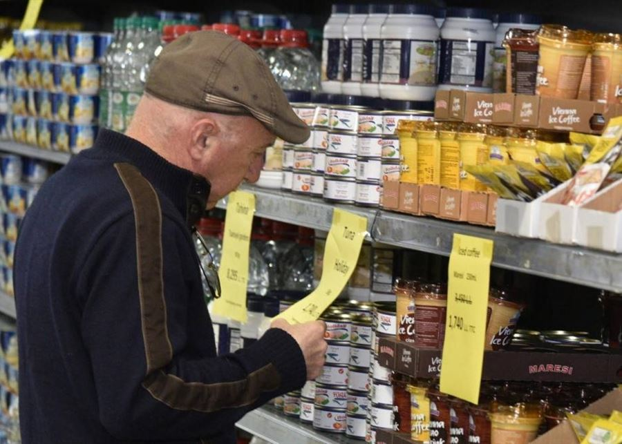 Old man looking at prices at the supermarket