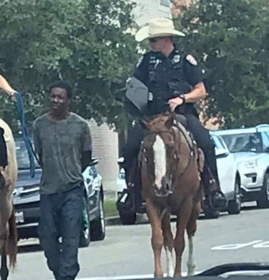 Black Man pulled by police officer on horse with a leash