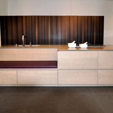 sandlbasted and smoked oak cabinetry with built-in upholstered bench featured in the eggersmann florida german kitchen showroom