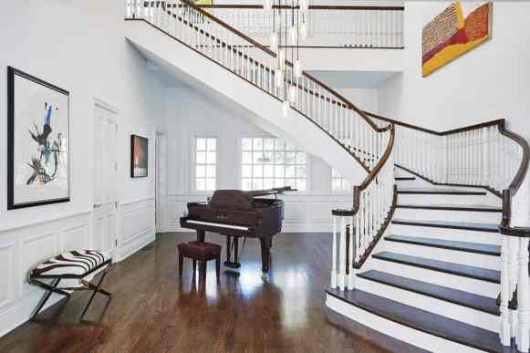 grand piano and stylish zebra bench in a stairwell foyer of a remodel project featuring a unique brass ring chandelier as shown in modern reduction in california home magazine