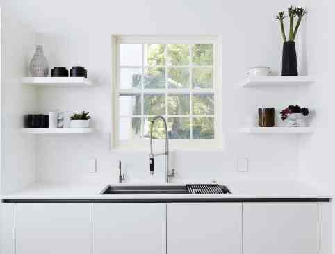 ultra modern white kitchen featuring the galley functional sink