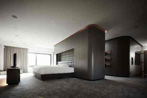 eggersmann cabinetry and clever design used to create a floating island wall full of storage to anchor the bed in this luxury master bedroom