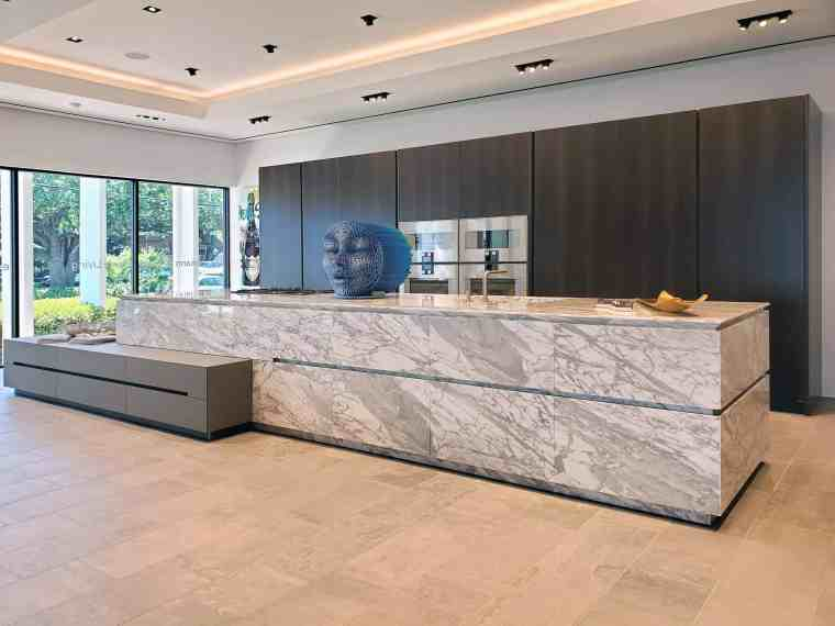curated art exhibition at eggersmann dallas featured this blue moon head sculpture by robert mars atop luxury cabinetry in the unique product line