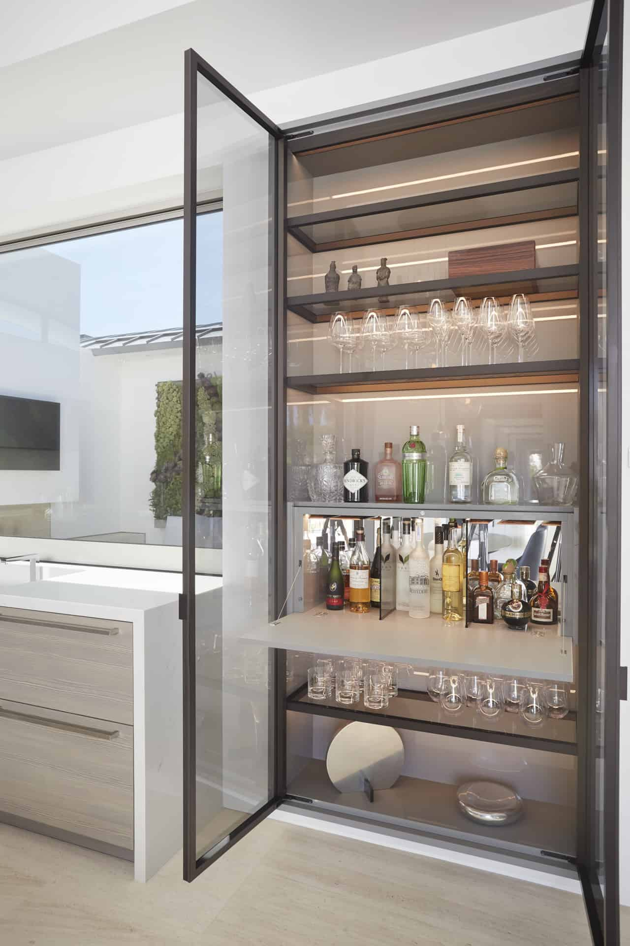 Floating glass-front bar cabinet is convenient as a pass-thru window to the courtyard
