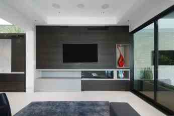 media room with eggersmann designed fireplace surround and display niches using a light concrete and dark wood to create interest