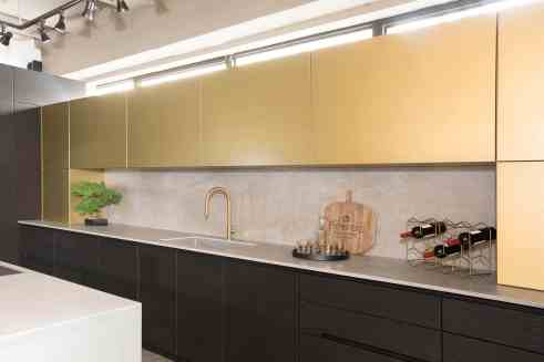 deep niche offers countertop space for small appliances and room for a gooseneck sink in this brass and stainless steel kitchen by eggesmann