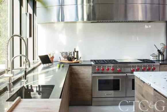 stainless steel, warm woods, and an indestructible solid surface counter creates a kitchen worthy of the cottage and gardens magazine