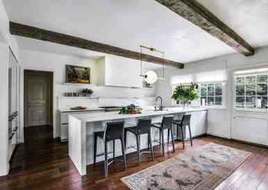 light bright marble kitchen accented by rough hewn beams and antique floor