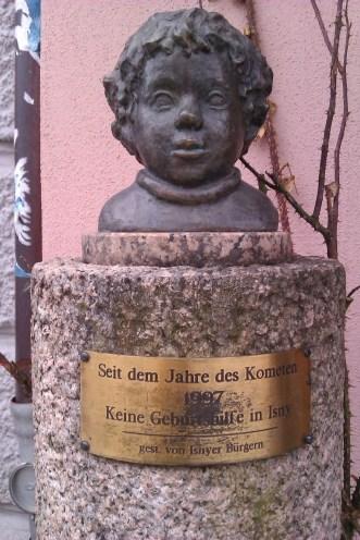 """Isny. Buste d'un enfant dans la rue principale. Un message énigmatique est inscrit sur la plaque : """"Depuis l'année de la comète (en 1997), plus d'aide à la naissance à Isny"""". La comète en question était celle de Hale-Bopp."""