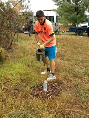 Shows VCE student from Baringa School watering mulched planting, Edward Hunter Heritage Bush Reserve