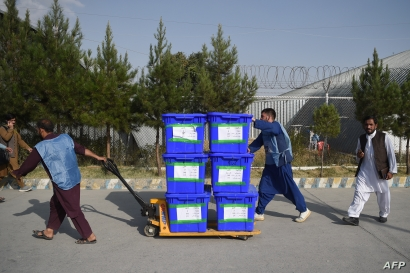 FILE - Independent Election Commission workers carry ballot boxes to be taken to a counting center in Kabul, Oct. 2, 2019.