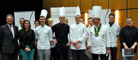 Die elf besten Koch-Azubis des Landes NRW traten in Kall zum zweitägigen Wettbewerb um die Teilnahme am Bundesentscheid in Frankfurt an. Sieger wurde Jan Semmelhack (Mitte, schwarze Kochjacke) vom Bonner Hotel Mameha Grand Bonn. (Bild: Reiner Züll)