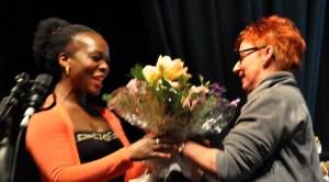 Carmen Keil von der Hilfsgruppe Eifel bedankt sich bei Sängerin Bwalya mit einem Bluemnstrauß. Foto: Reiner Züll