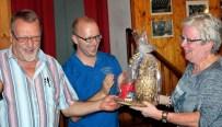 Turnierleiter Reiner Züll (links) übergibt seiner Ehefrau die Goldene Ananas als Schlusslicht. Bernd Jaschke von der VR-Bank applaudert. Foto: Patrick Züll