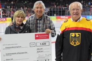 Scheckübergabe auf dem Eis. Willi und Kathi Greuel erhielten den Scheck aus den Händen von Dieter Züll. Bild: Reiner Züll