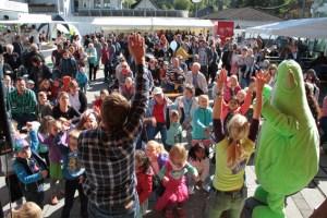Kinderliedermacher Uwe Reetz und das ene-Maskottchen Bene heizten den Kindern kräftig ein. Bild: Michael Thalken/Eifeler Presse Agentur/epa