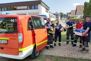 Kalls Löschzugführer Daniel Rütz (rechts) und Kleiderkammer-Chef René Jerratsch (2.v.l.) nahmen am Mittwoch die Schutzbekleidung von den drei Feuerwehr-Kollegen aus München entgegen. Foto: Reiner Züll
