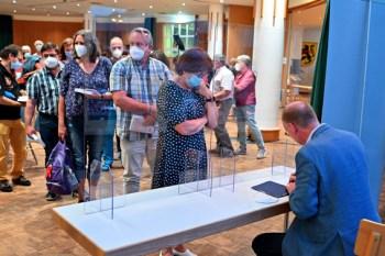 Buchsignierung hinter Plexiglas: Sven Plögers Autogramm war trotz Coronaregeln äußerst beliebt. Foto: Harald Tittel