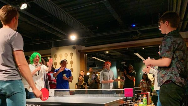 Millenials participating in 826DC's Paddlestar Galactica ping-pong tournament stand around a table at SPIN DC.
