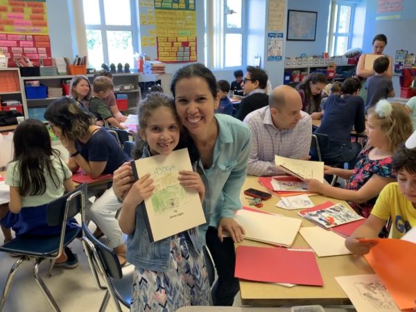 An Oyster Adams second grade student holds up her book about dogs.