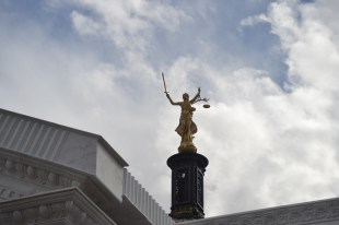 Lady Justice tops a copper dome with her sword at the ready to strike down injustice.