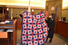 Vet wrapped in a Quilt of Valor by presiding veterans' court Judge Adrianna Escobar and the Nevada state coordinator for the Quilt of Valor Foundation, Victoria Colburn Hall.