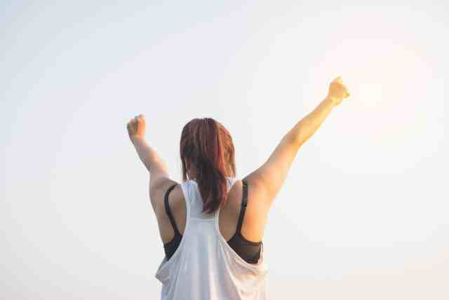 A motivated woman with her hands up excited at her achievements.