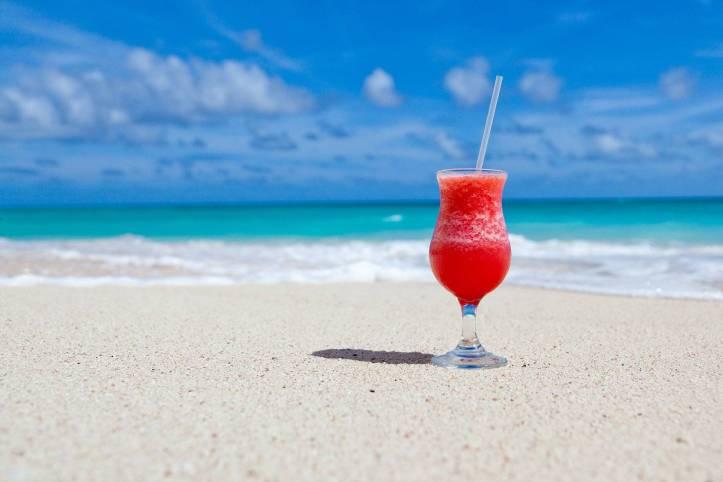 綺麗なビーチに赤い色のカクテルが置いてあります。後ろは切な海、青い空、気持ちいい - 函館英会話教室EigoLa - レッスン情報