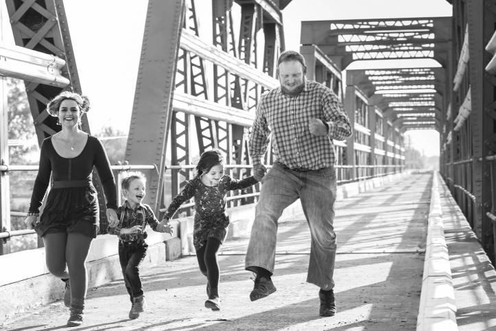 お母さん、お父さん、子供2人が手を繋ぎ、橋を渡っている。幸せそうな家族です。写真は白黒 - 函館英会話教室EigoLa - レッスン情報
