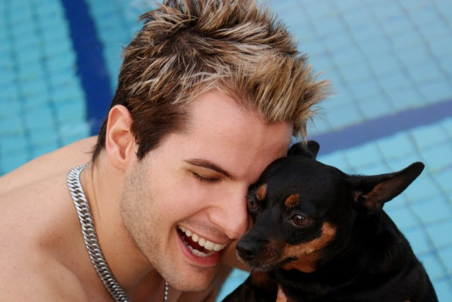 "Head shot of handsome young man smiling with his eyes closed and holding a dog (black and rust; perhaps a min pin) with their heads very close. Dog's ears are back, mouth is tight, and it does not look happy.The background appears to be a swimming pool. The photo appears ""slick"" and staged and is titled, ""True Friends."""