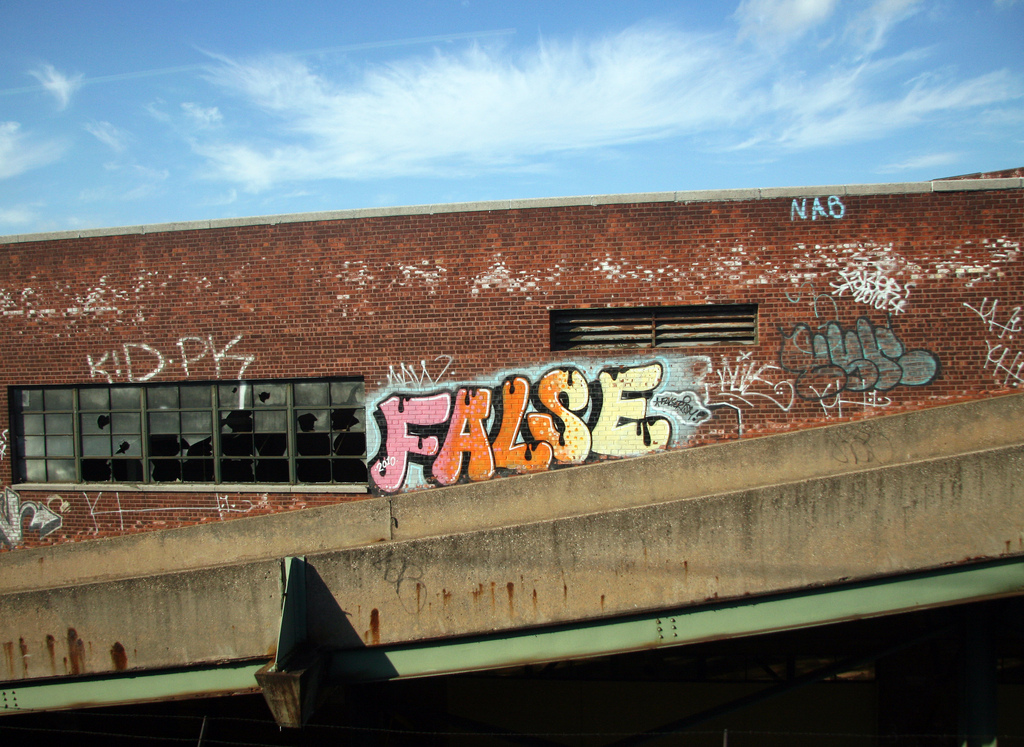 "Graffiti on a brick building that says, ""False"""