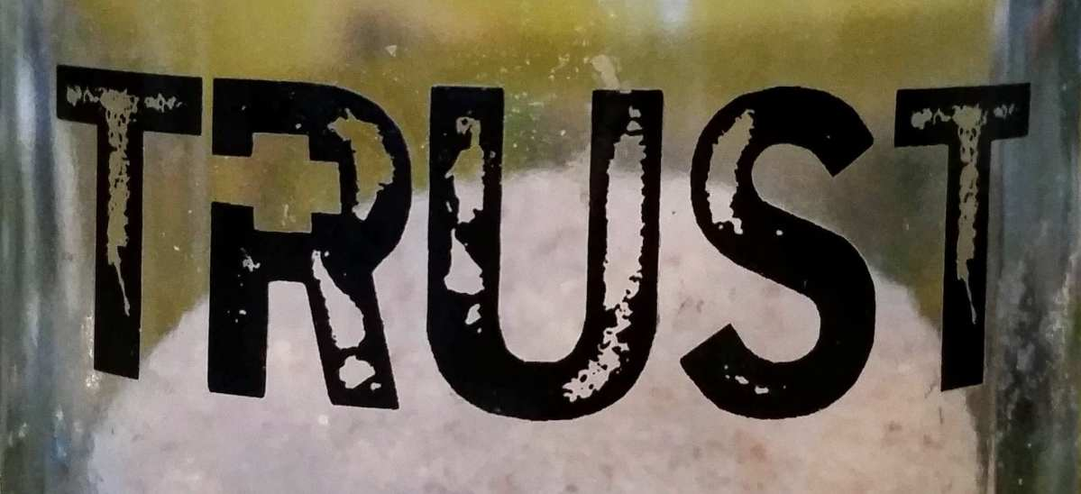 The word 'TRUST' printed in capital letters on curved glass