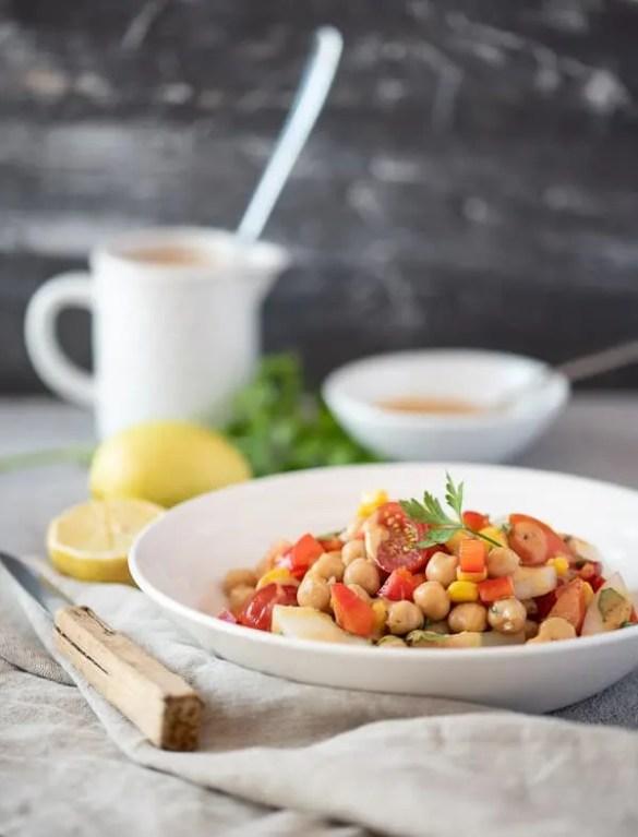 Bunter Salat mit Kichererbsen, Tomaten und Paprika auf einem weißen Teller