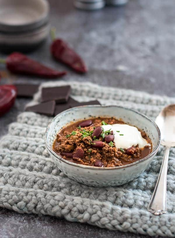 Chili con Carne mit Schmand und Kräutern in einer grauen Schüssel von vorne fotografiert.