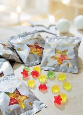 Weihnachtliche Fruchtgummi-Tüte mit duchsichtigem, großem Sternen-Motiv. Mit je 10g einer bunten Stern-Fruchtgummi-Mischung gefüllt, Maße: ca. 8,4 x 7 cm, Gewicht: ca. 0,7 kg. Zutaten: Glukosesirup, Zucker, 10% Fruchtsaft (Traube, Apfel, Birne, Pfirsich) aus Fruchtsaftkonzentraten, Gelatine, Säuerungsmittel: Zitronensäure, färbende Lebensmittel: Schwarze Johannisbeere, Karotte, Zitrone, Saflor, Spirulina, Aromen, Palmkernöl, Überzugsmittel: Bienenwachs weiß und gelb, Carnaubawachs. Nährwertangaben: Energie 1416 kJ/333 kcal; Fett 0,1g, davon gesättigte Fettsäuren 0,1g; Kohlenhydrate 76g, davon Zucker 43g; Eiweiß 6g; Salz 0,2g.<br>