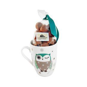 Die süße Tasse mit dem Motiv einer Zwinkereule beinhaltet 150 g feinster Nougat-Pralinen  2fach sortiert. Kakao: 38% mindestens in der Edel-Vollmilch-Schokolade, Maße: ca. L8 x B8 x H11 cm. Zutaten: Zucker, Kakaobutter, 13,0% Haselnusskerne, Vollmilchpulver, Macadamia-Nüsse, Kakaomasse, Magermilchpulver, Butterreinfett, Emulgatoren: Sojalecithin, Sonnenblumenlecithin; natürliches Aroma, Salz, Vanilleextrakt. Allergiehinweis: Kann Spuren weiterer Schalenfrüchte enthalten<br>