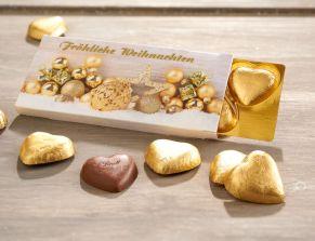 Der besondere Weihnachtsgruß. In der Präsent-Schachtel befinden sich fünf goldene Vollmilch-Schokoladen Herzen der Marke Lindt. Insgesamt ca. 25 g Schokolade, Maße: ca. B11,5 x T1 x H5,5 cm. Zutaten: Alpenvollmilch-Schokolade (Kakao: 30% mindestens): Zucker, Kakaobutter, VOLLMILCHPULVER, Kakaomasse, MILCHZUCKER, MAGERMILCHPULVER, Emulgator (SOJALECITHIN), GERSTENMALZEXTRAKT, BUTTERREINFETT, Aroma Vanillin. Allergiehinweis: Kann Spuren von Haselnüssen und Mandeln enthalten<br>