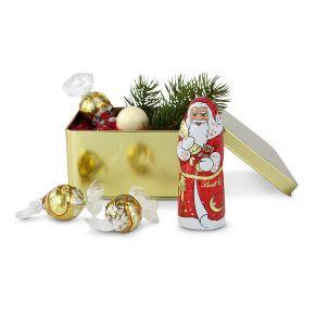 Diese kleine goldfarbene Dose hat einen goldig-weihnachtlichen Inhalt: 1 Lindt Weihnachtsmann (40 g) und 3 weiße zartschmelzende Lindorkugeln, gewickelt in goldenes Papier. Maße: ca. L14,2 x B10,5 x H7,1 cm. Zutaten: Lindor Kugel weiß, Zucker, Kakaobutter, pflanzliches Fett (Kokosnuss, Palmkern), Vollmilchpulver, Magermilchpulver, Emulgator (Sojalecithin), Aromen., , Weihnachtsmann, 40g, Zucker, Kakaobutter, Vollmilchpulver, Kakaomasse, Milchzucker, Magermilchpulver, Emulgator (Sojalecithin), Gerstenmalzextrakt, Butterreinfett, Aroma Vanillin.. Nährwertangaben: Lindor Kugel weiß, Nährwerte  pro 100 g   % der RM* pro 100 g, Brennwert:  2691 kJ (643 kcal)    32,0 %, Fett:  52,00 g   74,29 %, davon:, – gesättigte Fettsäuren:   , 37,00 g    185,00 %, Kohlenhydrate:  40,00 g     15,38 %, davon:, – Zucker:   , 40,00 g      44,44 %, Eiweiß:  5,10 g     10,20 %, Salz:  0,20 g      3,33 %, , , Weihnachtsmann, 40g, Nährwerte  pro 100 g   % der RM* pro 100 g, Brennwert:  2294 kJ (548 kcal)  27,3 %, Fett:  33,00 g   47,14 %, davon:, – gesättigte Fettsäuren:   , 20,00 g    100,00 % , Kohlenhydrate:  55,00 g   21,15 %, davon:, – Zucker:   , 55,00 g    61,11 % , Eiweiß:  7,20 g   14,40 %, Salz:  0,20 g   3,33 %, , *) RM = Referenzmenge für einen durchschnittlichen Erwachsenen (8.400 kJ/2.000 kcal).. Allergiehinweis: Lindor Kugel weiß Enthält Soja, Milch, Lactose und glutenhaltige Getreide. Kann Haselnüsse und Mandeln enthalten.  Weihnachtsmann, 40g Glutenhaltige Getreide, Milch und Laktose, Schalenfrüchte. Kann Haselnüsse und mandeln enthalten.