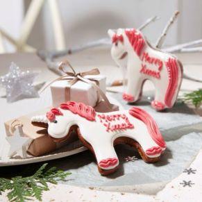 """Weihnachtliches Einhorn mit roter Mähne und Schweif, sowie einem Weihnachtsgruß. Aufschrift """"Merry XMAS"""", einzeln in Folie eingeschweißt, Maße: ca. 13 x 9 cm. Zutaten: WEIZENMEHL, Invertzuckersirup, Zucker, ROGGENMEHL, Feuchthaltemittel: Sorbitsirup,"""