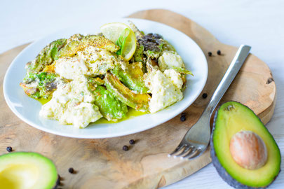 Auf diesem Bild ist ein warmer Avocado - Feta Salat zu sehen. Der Salat liegt auf einem weißen Teller welches auf einem alten Holzbrett steht.