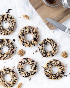 Hier sind schnelle Schoko - Apfelringe zu sehen, die mit zuckerfreier Schokolade überzogen wurden und mit Samen und Nüsse bestreut wurden.