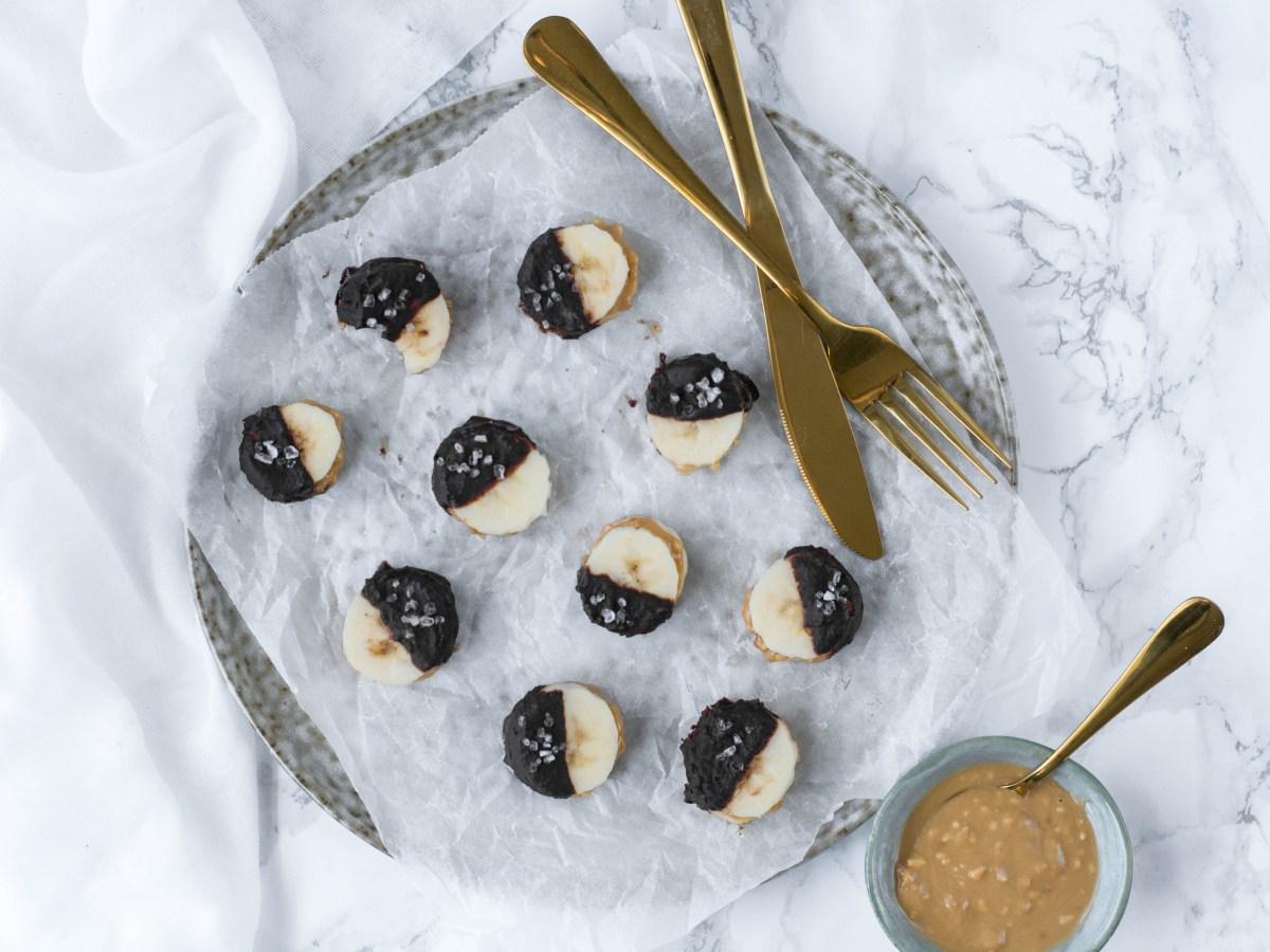Auf diesem Bild ist eine gefrorene Snickers Banane zu sehen. Die Banane wurde in Scheiben geschnitten, mit Erdnussmus bestrichen und in zuckerfreie Schokolade getunkt.