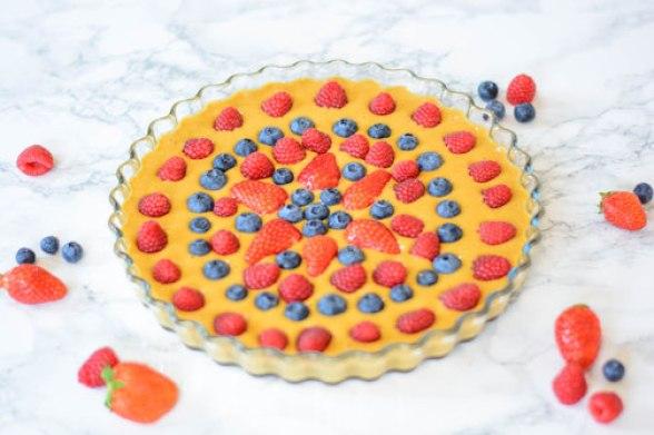 Zuckerfreier Beerenkuchen von schräg oben fotografiert. Die Kuchenform steht auf einer weißen Marmorplatte und daneben liegen frische Beeren.