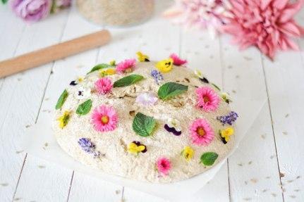 Brot mit Blumen dekoriert. Im Hintergrund steht das frische Getreide.