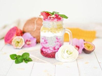 Auf diesem Bild ist ein Chiapudding mit Drachenfrucht und Maracuja. Das Bild wurde von vorne fotografiert. Im Hintergrund liegt frisches Obst und Blumen.