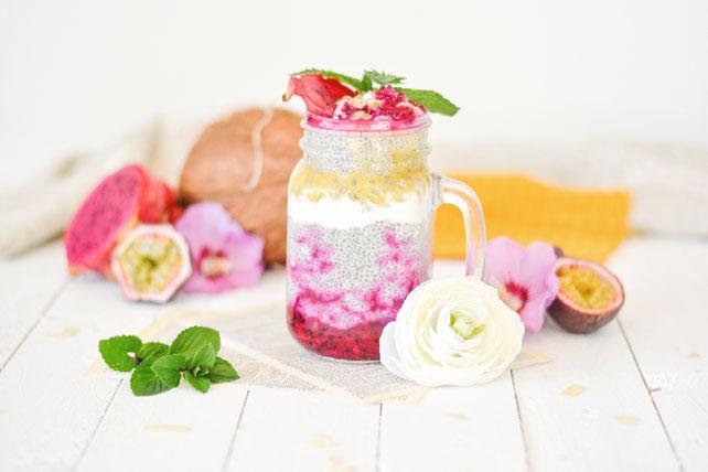 Auf diesem Bild ist ein Chiapudding mit Drachenfrucht und Maracuja zu sehen. Der Chiapudding ist schön angerichtet in einem Glas. Daneben liegen die frischen Früchte und eine Blume.