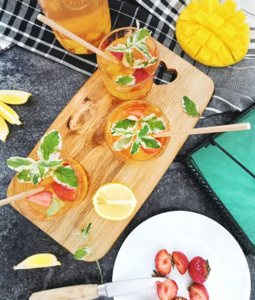 Zuckerfreier Mango - Erdbeer Eistee von oben fotografiert. Der Eistee ist ein kleine Gläser abgefüllt und steht auf einem Holzbrett.