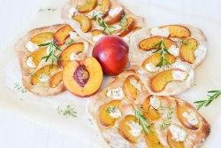 Gegrillter Flammkuchen mit Pfirsich und Ziegenfrischkäse von oben fotografiert. In der Mitte liegt ein aufgeschnittener Kürbis und dekoriert sind die Flammkuchen mit Rosmarin.